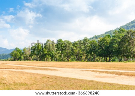 Landscape of meadow,forest and mountain under the blue sky and white clouds. - stock photo