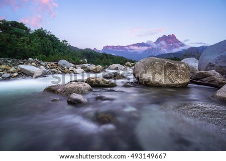 Landscape of Melangkap river with transparent water,rocky bottom and with Mount Kinabalu at the background during sunset in Kota Belud,Sabah,Borneo,Malaysia.
