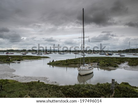 Landscape of moody evening sky over low tide marine full of yachts - stock photo