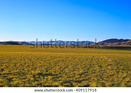 Landscape of mountains and farmland with snow covered peaks. - stock photo