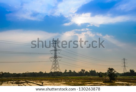 Landscape of paddy field and high voltage electricity pole with sunset - stock photo