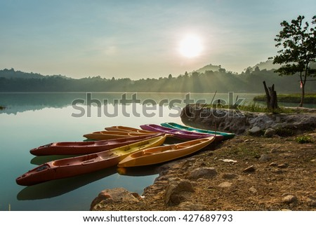 Landscape of Plastic kayak in the sunrise lake with flare in the morning.