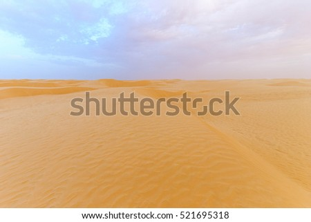 Landscape of Sahara desert with cloudy sky at evening. Sand dunes Tunisia.