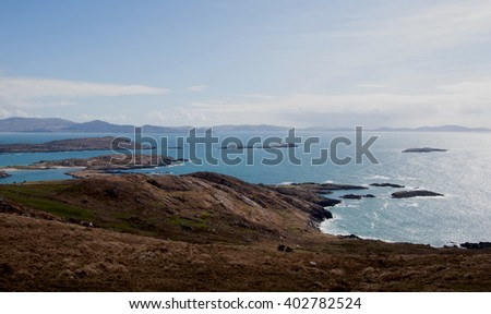Landscape of the Caherdaniel Village area of the Ring of Kerry, Ireland. Blue ocean water, brown hills, blue sky with scattered clouds - stock photo