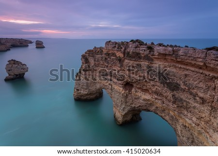 Landscape of the South Coast of Portugal at Sunrise. Marinha Beach is a holiday destination for its beautiful beaches with cliffs and hot water. The arch carved in stone is an amazing senary