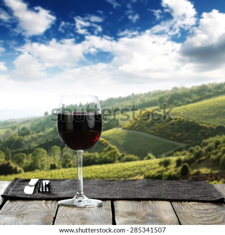 Landscape of Tuscany and sigle glass of wine