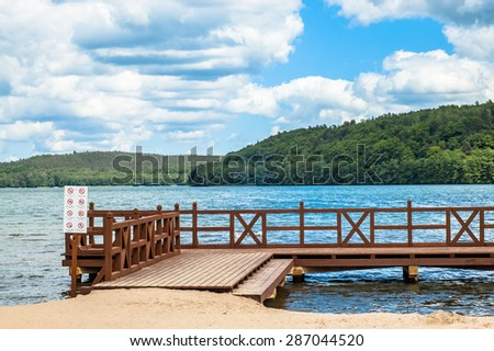 Landscape of wooden pier over beautiful lake in the summer. Vacation and holiday time, nature composition or postcard.