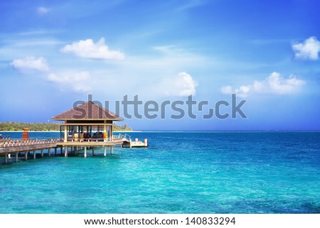 Landscape photo of Island in ocean, overwater villa with endless swimming pools. Maldives.