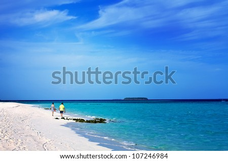 Landscape photo of  Romantic happy senior man and woman couple walking on a tropical beach with bright clear blue sky - stock photo