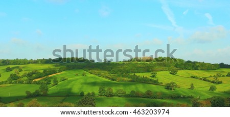 Landscape photo of very green hillside in Cotswolds, England.
