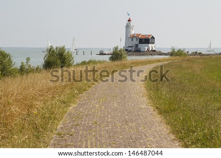 Landscape photo showing a dyke leading up to a beautiful old lighthouse. - stock photo