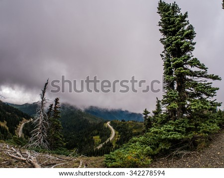 Landscape photo shows Highway up to Hurricane Ridge with fog covered mountains behind - stock photo