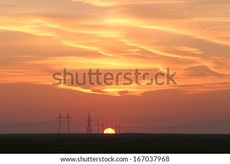landscape power lines against the background of a beautiful sunset - stock photo
