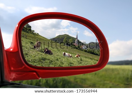 Landscape reflected in the rear view mirror of a red car - summer series  - stock photo