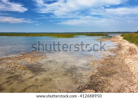 Landscape - sandy beach, clouds over lake with clear water and sandy bottom. - stock photo