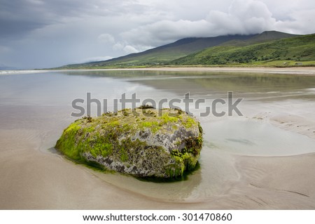 Landscape scene on the west coast of Ireland with dramatic broken storm clouds reflections in sea beside isolated weedy rock on a deserted sandy beach during stormy weather in summer in county Kerry. - stock photo