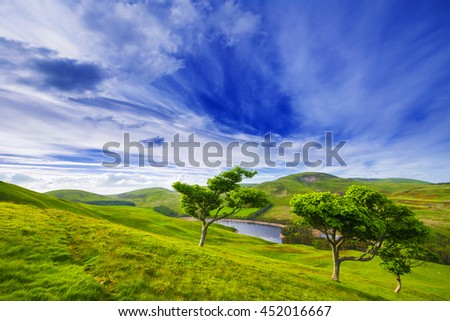 Landscape scenery of green valley with trees, river and cloudy blue sky. Pentland hills, Scotland