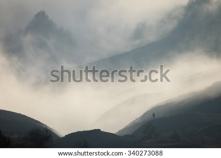 Landscape. Silhouette of a man in a fog against the backdrop of mountain slopes - stock photo