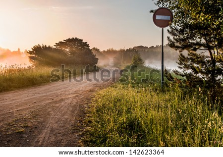 Landscape, sunny dawn with road, fog and road sign - stock photo
