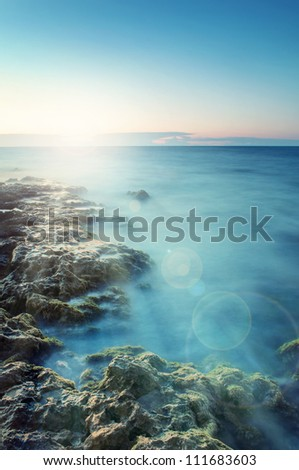 landscape sunset or sunrise on the sea with stones in the foreground