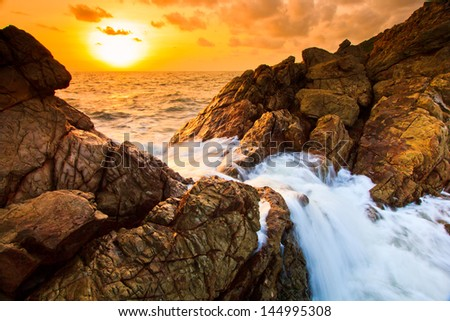 Landscape  sunset sea waves line impact rock on the beach