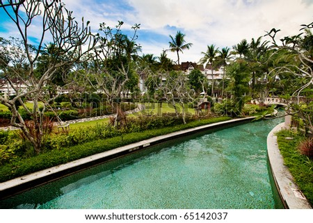 Landscape swimming pool within compound of tropical resort hotel.
