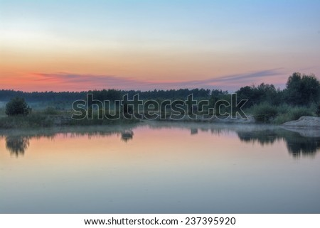 Landscape - Twilight on the lake, the forest in the background and fog on the coast - stock photo