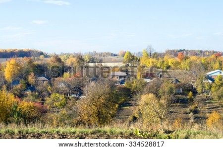 Landscape - view edge of the village near the autumn forest
