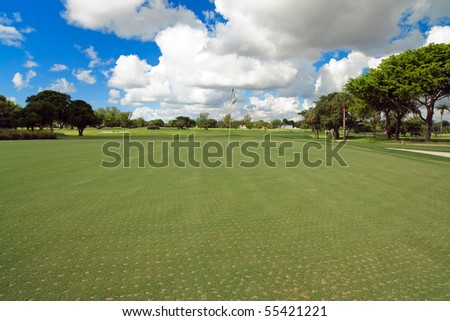 Landscape view of a freshly aerated golf course putting green on the 18th hole.