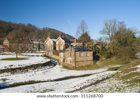 Landscape view of a rural english countryside village scene with traditional cottages and stream - stock photo