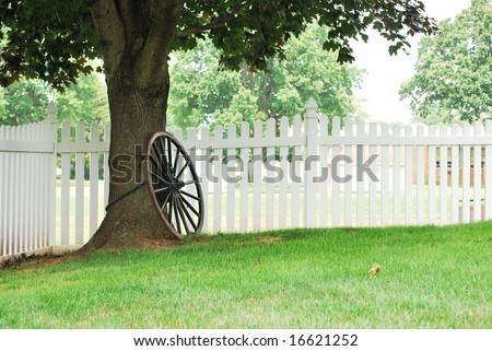 Landscape view of an old spoked wheel chained to a tree