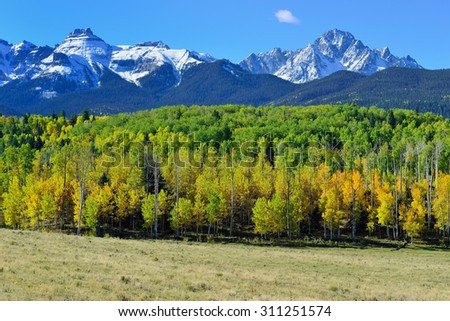 landscape view of the colorful alpine scenery with snow covered mountains during foliage season