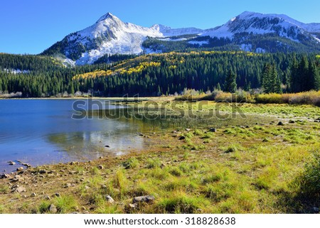 landscape view of the colorful alpine scenery with snow covered mountains during foliage season at Kebler and Ohio Passes