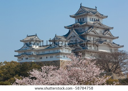 Landscape view of the main tower of Himeji Castle on the hillside during the daytime with bonsai pine trees of the castle gardens in the foreground and blue sky in the background - stock photo