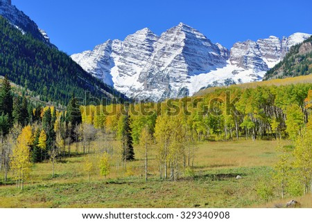 landscape view of the snow covered mountains with colorful yellow aspen during foliage season in Colorado - stock photo