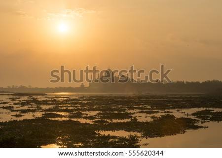 Landscape view of Yamuna River during sunrise with soft image background of Taj Mahal in Agra, India.