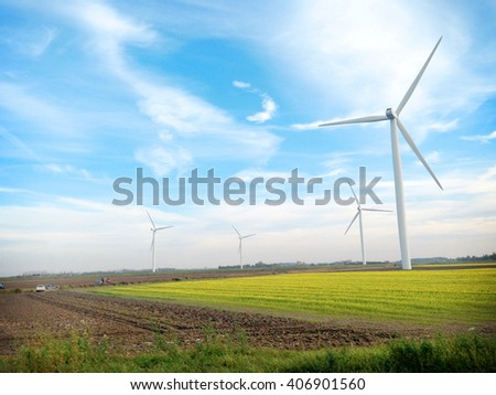 Landscape view Wind Turbine farms among the yellow flower field contrast with vivid blue sky color, Zeeland , The Netherlands  - stock photo