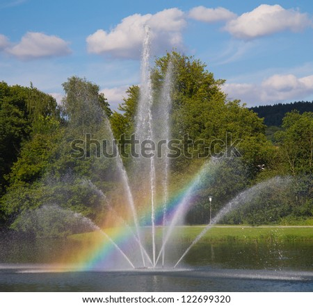 Landscape with a Beautiful Rainbow in a Fountain - stock photo