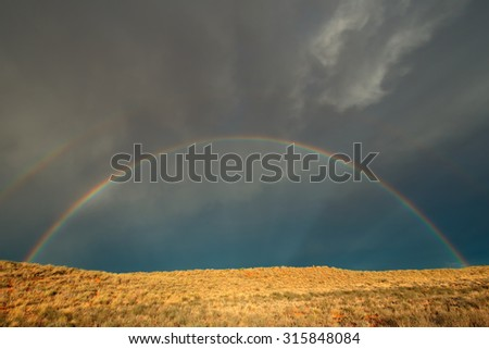 Landscape with a colorful rainbow in stormy sky, Kalahari desert, South Africa - stock photo