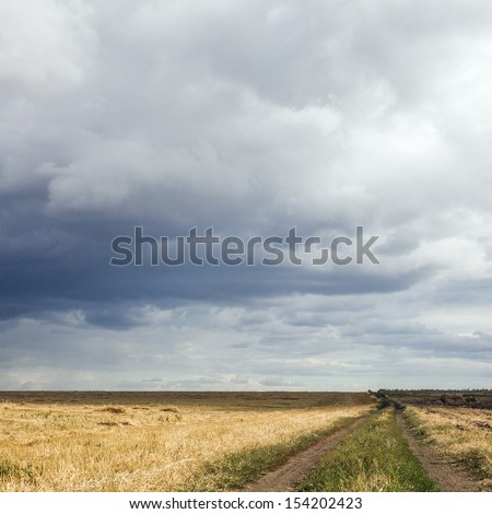 landscape with a dark sky and a country road