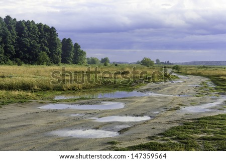 Landscape with a dirt road after rain - stock photo