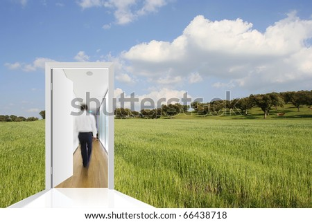 landscape with a green field and blue sky with a door to the office - stock photo