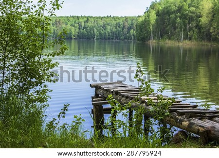 landscape with a lake, forest and wooden walkways - stock photo