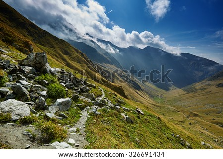 Landscape with a marked hiking trail in the mountains - stock photo