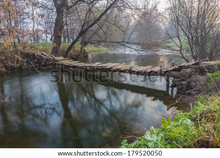 landscape with a wooden bridge over the river - stock photo