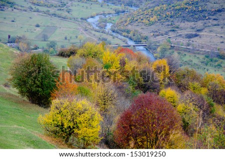 Landscape with autumn trees and flowing river - stock photo