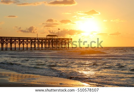 Landscape with beautiful golden sunrise over Atlantic ocean, wooden pier on the background.