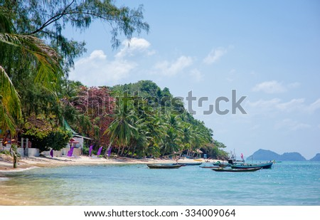 Landscape with beautiful tropical beach with palms and longtail boats. Pangan Thailand.