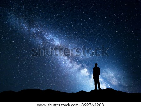 Landscape with blue Milky Way. Night sky with stars and silhouette of a happy man on the mountain. Beautiful Universe. Space background - stock photo