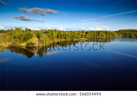 Landscape with blue sky and smooth lake surface - stock photo